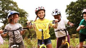 Group of kids standing with bicycle and giving high five