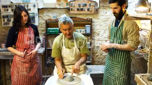 Colleagues looking at potter while making a earthen pot on a pottery wheel