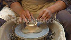 Potter making a earthen pot on a pottery wheel
