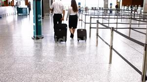 Pilot and female flight attendant walking with luggage