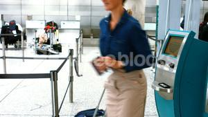 Female commuters using airline ticket machine