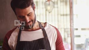 Smiling waiter holding glass of cold coffee at counter in cafe