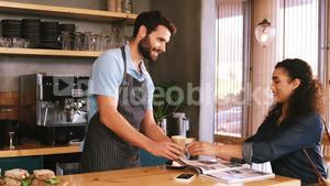 Waiter serving a glass of cold coffee to customer at table