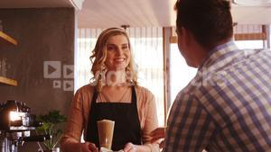 Waitress serving a glass of cold coffee to customer