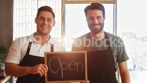 Smiling waiters showing slate with open sign
