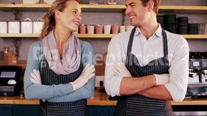 Waiter and waitress standing with arms crossed and smiling at each other