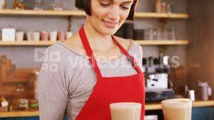 Smiling waitress carrying two cold coffees in cafe