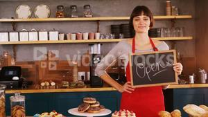 Smiling waitress showing a open sign board