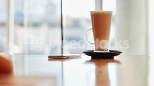 Glass of coffee and mobile phone on table