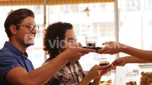 Waitress serving black tea to two friends