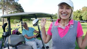 Female golf player interacting with man