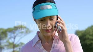 Female golf player talking on mobile phone while playing golf