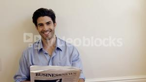 Smiling man reading business newspaper at home