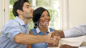 Happy couple signing contract with real estate agent