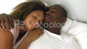 Young couple sleeping together on bed