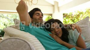 Young couple sleeping together on sofa