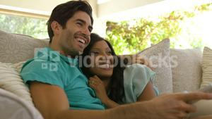 Young couple watching tv on sofa in living room