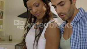 Young couple looking at recipe book in kitchen