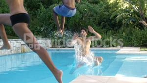 Group of friends jumping in swimming pool