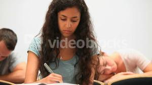 Serious students taking notes while their classmate is sleeping