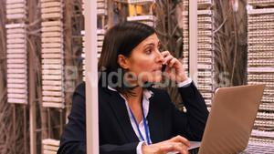 Technician talking on mobile phone while using laptop