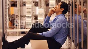 Stressed technician sitting in hallway