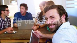 Business people discussing over digital tablet and laptop