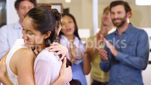 Two womens hugging each other while colleagues clapping in background