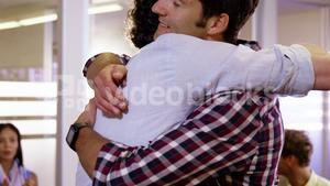 Two mens hugging each other while colleagues clapping in background