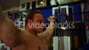 Man exercising with high cable bicep curl