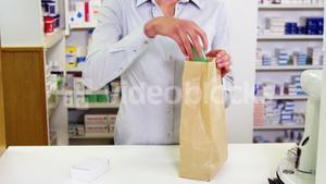 Pharmacists packing medicine in paper bag