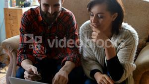 Couple shopping online on laptop in living room