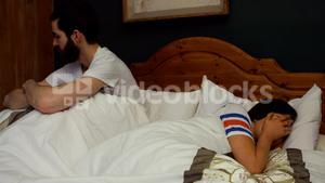 Couple ignoring each other on bed in bedroom