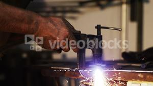 Hands of welder using welding torch