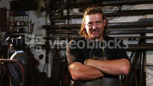 Welder standing with arms crossed