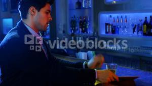 Well dressed man drinking whisky and using digital tablet at counter