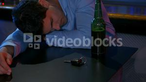Drunk man sleeping with his head on counter