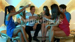 Man popping a champagne bottle and pouring it in friends glass