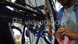 Mechanic cleaning bicycle spoke in workshop