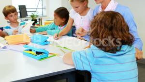Teacher helping kids with their homework in classroom