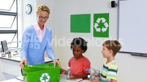 School kids looking recycle logo box in classroom