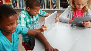 Group of school kids using digital tablet and laptop in library