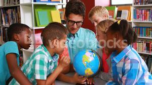 Kids and teacher looking at globe in library