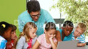 Teacher and kids using laptop in classroom