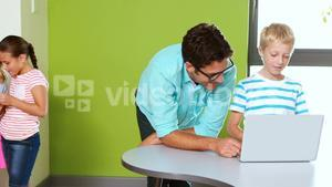 Teacher and schoolboy using laptop in classroom