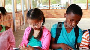 Group of school kids using digital tablet and laptop in campus