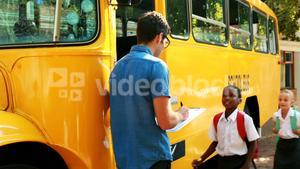 Teacher taking attendance while student entering in bus