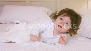 Cute baby girl playing on bed