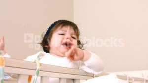 Close-up of baby girl in baby cot