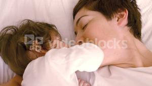 Mother playing with her baby on bed